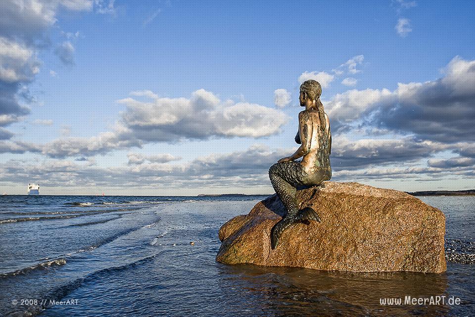 Travemünder Meerjungfrau auf einem Stein am Strand // Foto: MeerART