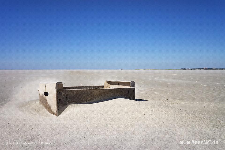 Eine angespülte Holzkiste auf einer Sandbank im Watt vor St. Peter Ording // Foto: R. Kerpa