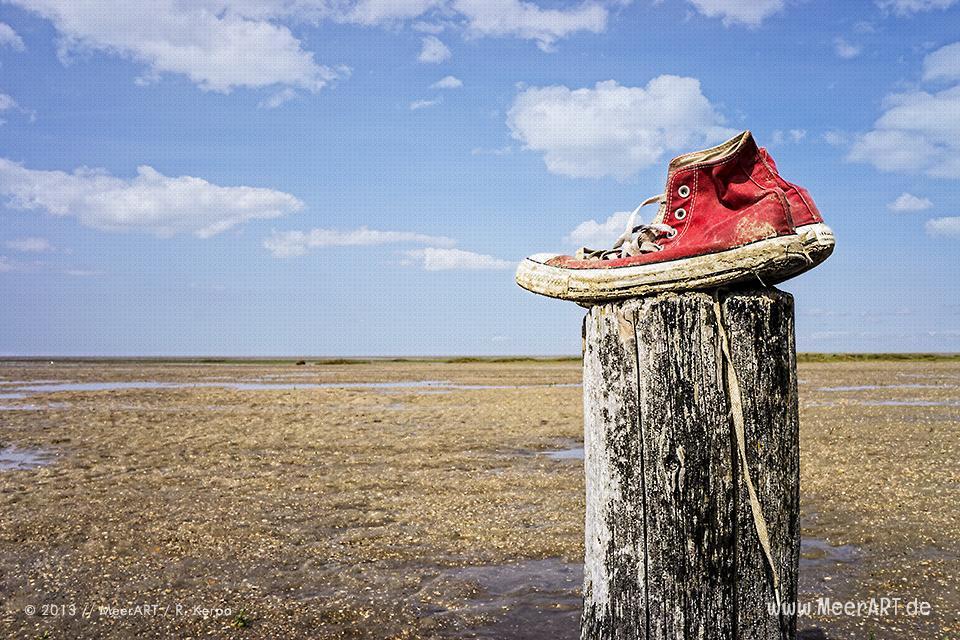 Zurückgelassene Sneaker auf einem Holzpfahl am Strand // Foto: R. Kerpa