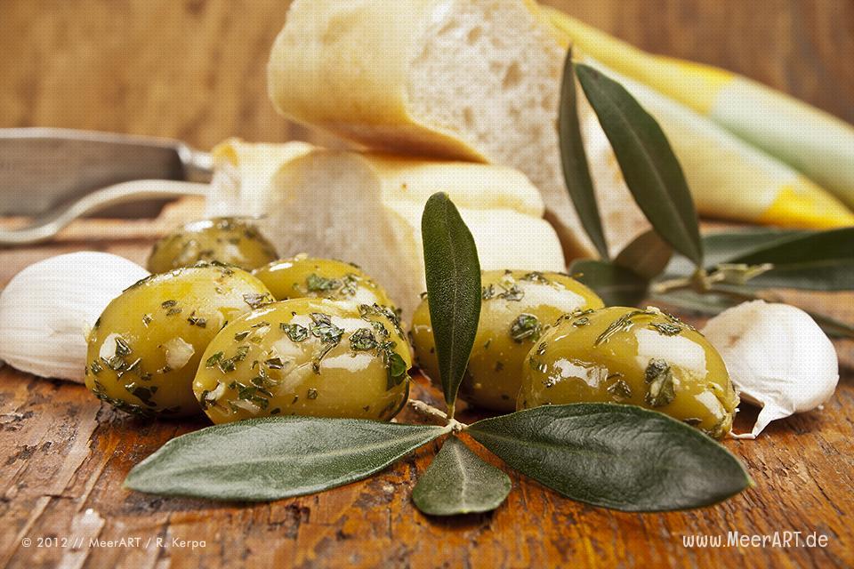Grüne Oliven mit einem Olivenzweig, Brot und Knoblauch // Foto: R. Kerpa