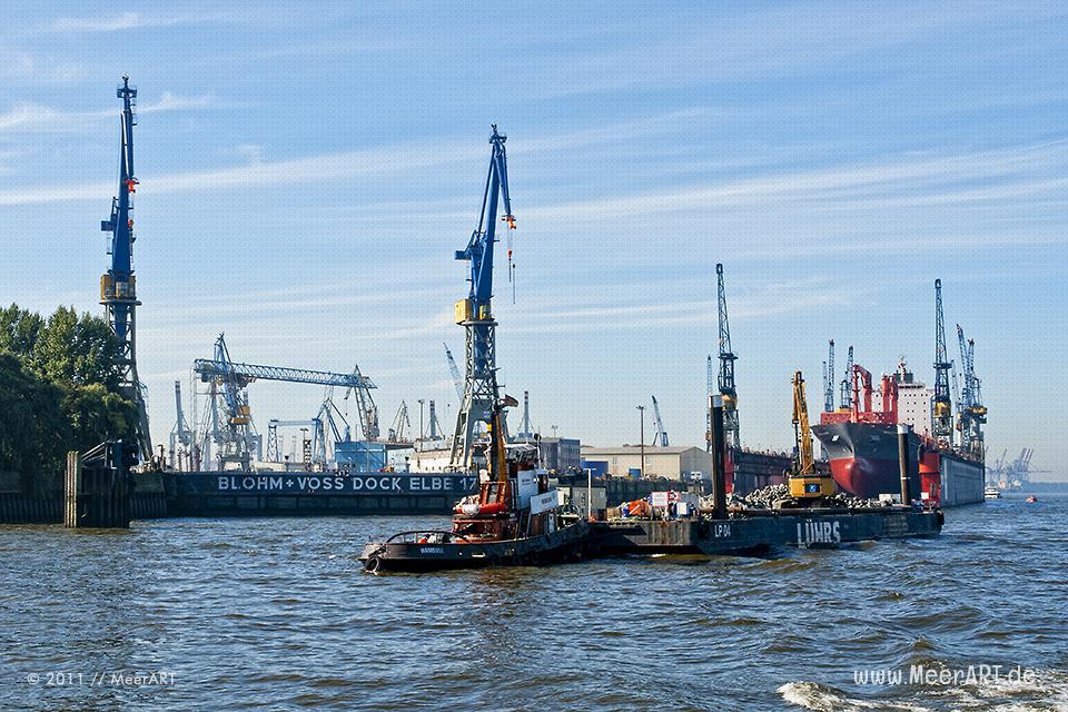 Ein Schlepper mit einem Arbeitsponton und einem Bagger vor den Docks von Blohm+Voss im Hamburger Hafen // Foto: MeerART