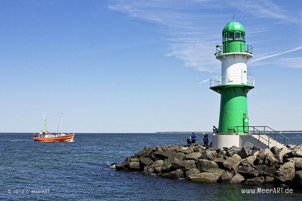 Ein Kutter läuft in den Hafen von Warnemünde ein, davor der grün-weiße Leuchtturm auf der Mole // Foto: MeerART