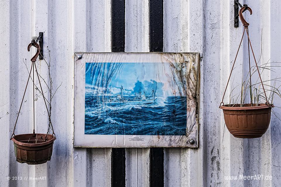 """Ein ausgeblichenes Bild der """"MS Bleichen"""" in einem Rahmen und zwei Blumentöpfe // Foto: MeerART"""
