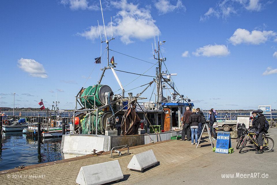 Ein Fischer verkauft fangfrischen Fisch direkt vom Fischkutter an seine Kunden im Hafen von Heikendorf/Möltenort // Foto: MeerART