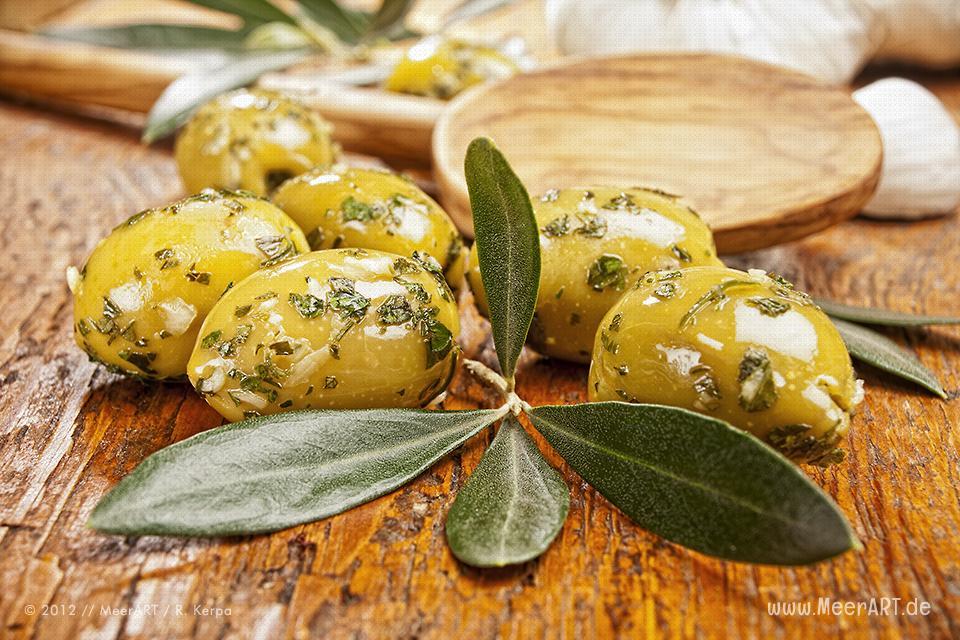 Grüne Oliven mit einem Olivenzweig, im Hintergrund ein Holzlöffel und Knoblauch // Foto: R. Kerpa