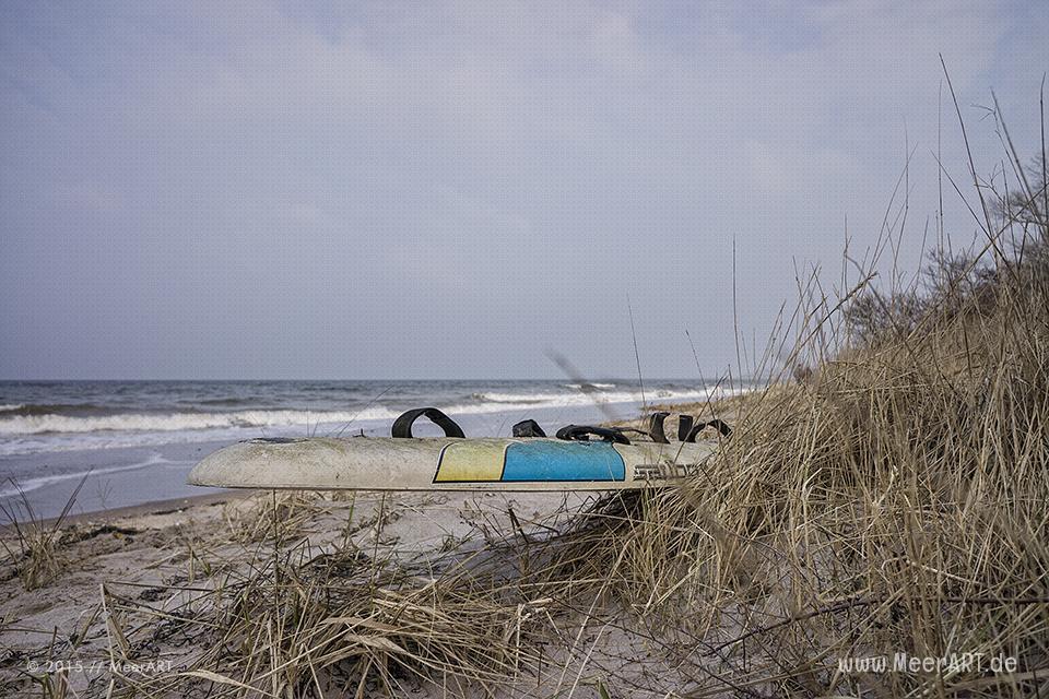 Eine angespültes Surfbrett an einem Strandabschnitt auf der Halbinsel Priwall // Foto: MeerART