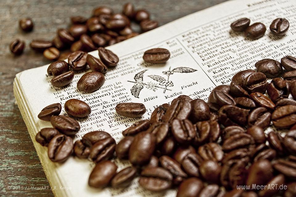 Ein altes aufgeschlagenes Lexikon mit Kaffeebohnen auf einem Holztisch // Foto: R. Kerpa