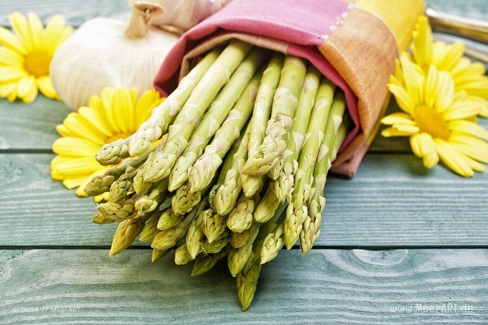 Grüner Spargel in einer Stoffserviette, anbei Knoblauch und ein paar gelbe Blüten // Foto: MeerART